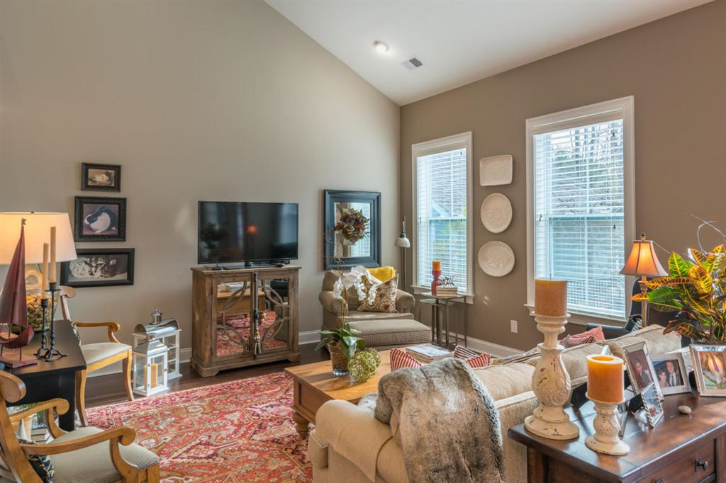 Huge family room with two large windows and a red carpet, soaring ceilings.