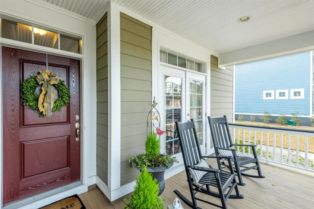 Front porch with plants and two rocking chairs.
